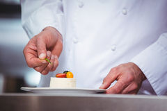 Chef putting finishing touch on dessert Stock Photo