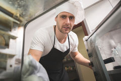 Chef putting food out from oven Royalty Free Stock Image