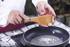 Chef putting garlic and red onuion to the pan Stock Images
