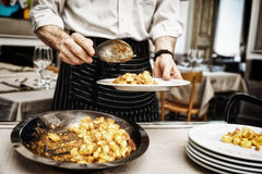 Chef is putting gnocchi with meat in plates, toned Stock Images