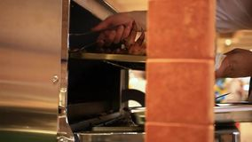 Chef putting meat into oven in the kitchen. HD stock video