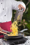 Chef putting noodle to pa Royalty Free Stock Images