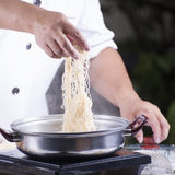 Chef putting the noodle to the pot Stock Photos