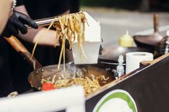 Chef putting noodles in carton box to go from pan on fire at open kitchen. Fried chinese japanese noodles with vegetables and royalty free stock photo