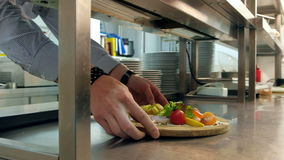 Chef putting prepared dish on the counter for waiter to take away stock video footage
