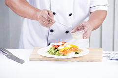Chef putting salad dressing Royalty Free Stock Image