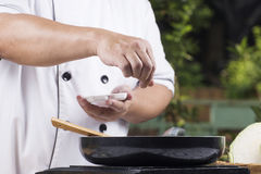 Chef putting Salt to the pan for cooking Royalty Free Stock Photos