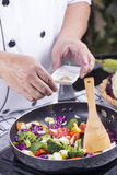 Chef putting Salt to the pan for cooking Stock Image