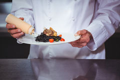 Chef putting sauce on a dish of spaghetti. In commercial kitchen Stock Photography