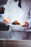 Chef putting sauce on a dish of spaghetti Royalty Free Stock Photos