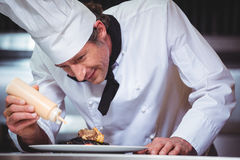 Chef putting sauce on a dish of spaghetti. In commercial kitchen Stock Photos