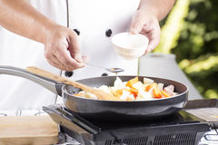 Chef putting seasoning sauce to the pan for cooking Japanese por Stock Photography