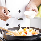 Chef putting seasoning sauce to the pan for cooking Japanese por Royalty Free Stock Photo