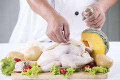 Chef putting a seasoning to raw chicken Royalty Free Stock Images