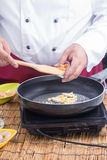 Chef putting slice of dried radish to pan Royalty Free Stock Photography