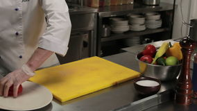 Chef putting sliced tomato on a plate, medium shot. Chef in restaurant putting sliced into rings fresh tomato on a plate, medium shot stock footage