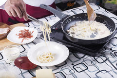 Chef putting Spaghetti carbonara to the plate with tongs Royalty Free Stock Image