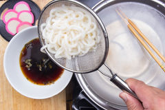 Chef putting udon noodle to cup Royalty Free Stock Images