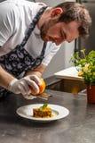 Chef rasping orange zest Royalty Free Stock Photography
