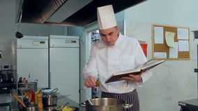 Chef reading cook book and making some dish stock video footage