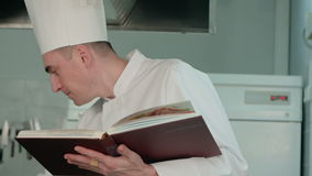 Chef reading cook book and preparing ingredients stock footage