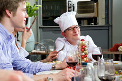 Chef receiving compliments. Restaurant guests talking to the chef during dinner Stock Photo