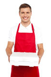 A chef in red uniform offering you a pizza box Royalty Free Stock Photos