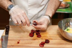 Chef is removing stones from cherry Royalty Free Stock Photos