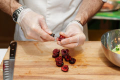 Chef is removing stones from cherry Stock Photo
