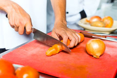 Chef in restaurant kitchen cooking. Asian Indonesian chef along with other cooks in restaurant or hotel commercial kitchen cooking, slicing a carrot Royalty Free Stock Photos