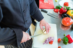 Chef in restaurant kitchen cutting onions Royalty Free Stock Photos