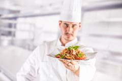 Chef in restaurant kitchen holding plate with italian meal spagh. Etti bolognese royalty free stock image