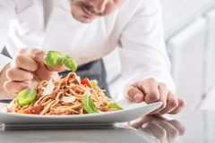 Chef in restaurant kitchen prepares and decorates meal with hands.Cook preparing spaghetti bolognese stock image