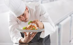 Chef in restaurant kitchen prepares and decorates meal with hands.Cook preparing spaghetti bolognese stock photos