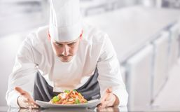 Chef in restaurant kitchen prepares and decorates meal with hands.Cook preparing spaghetti bolognese royalty free stock images