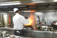 Chef in restaurant kitchen at stove with pan Stock Photography