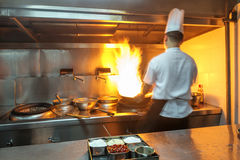 Chef in restaurant kitchen at stove with pan Stock Images