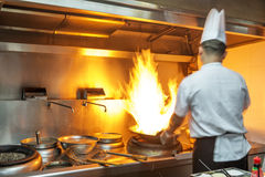 Chef in restaurant kitchen. At stove with pan, doing flambe on food royalty free stock photos