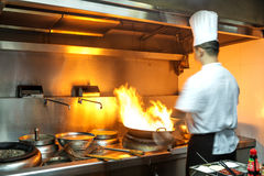 Chef in restaurant kitchen at stove with pan Royalty Free Stock Image
