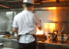 Chef in restaurant kitchen at stove with pan Royalty Free Stock Images