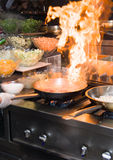 Chef in restaurant kitchen at stove with pan, doing flambe on food. low ligth selective focus. Royalty Free Stock Photos