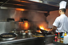 Chef in restaurant kitchen at stove with pan Stock Photos