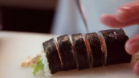 Chef in restaurant preparing and Cutting sushi rolls stock footage