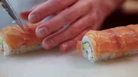Chef in restaurant preparing and Cutting sushi rolls stock video