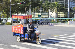 Chef riding a tricycle selling snacks Royalty Free Stock Photography