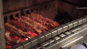 The chef roasts grilled various kinds of meat over charcoals in the restaurant. The cook stokes the fire with poker and shove live coals aside. Pieces of meat stock footage