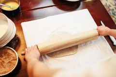 Chef roll out the dough with rolling pin, top view. Male chef roll out the dough with a rolling pin, top view, wooden kitchen table on background. Homemade Stock Images
