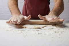 Chef rolling dough with rolling pin stock photo
