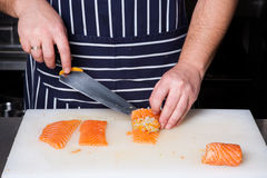 Chef rolling up salmon fillets. On a cutting board Royalty Free Stock Photography