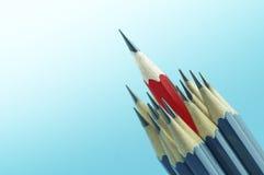 Chef rouge de crayon sur le fond bleu, concept différent Photos libres de droits